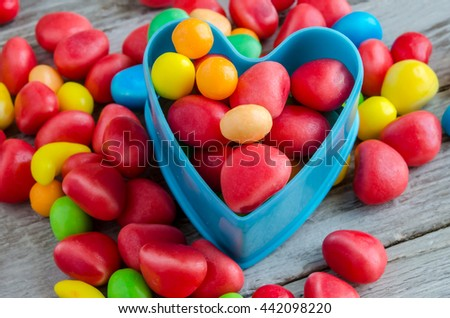 Close-up of bright multicolored sweets and candies scattered on wooden table - stock photo