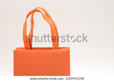 Close up of bright orange recycle paper bag with design for carrying and putting gift or present for special event - stock photo