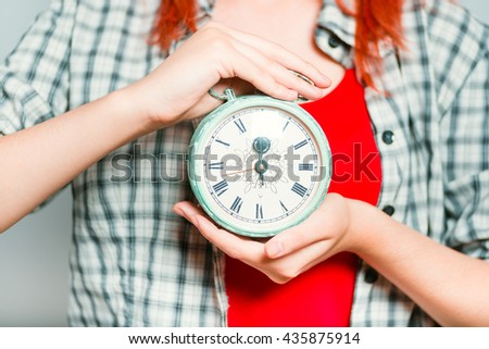 close-up of bright red haired girl shows time on a retro alarm clock