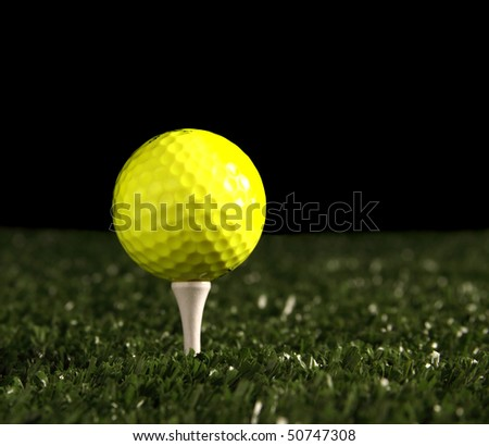 Close up of bright yellow golf ball on white tee in the ground, (artificial turf) green grass fading into a black backround(for copy), shallow depth of field with focus point on the front of the ball - stock photo