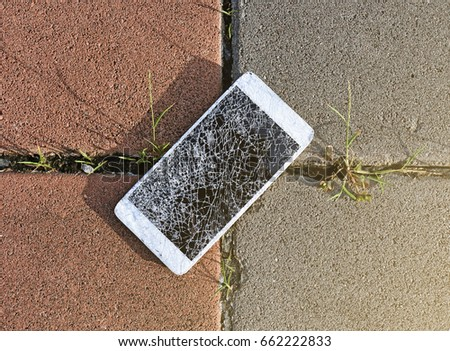 Close up of broken mobile phone drop on stone paved sidewalk outdoors