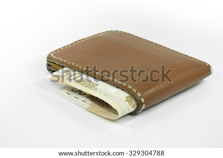 Close up of brown leather wallet with money, on white background