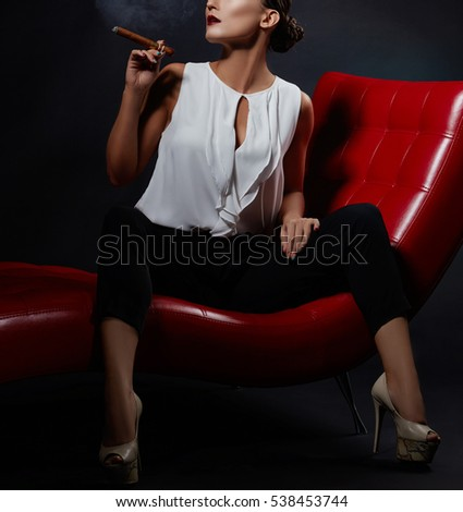 Close-up of brunette woman in business style with cigar on red chair over smoky dark background. Studio portrait.