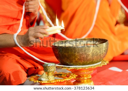 close up of buddhist monk's hand pouring melt candle tears to the water for making blessing water  - stock photo