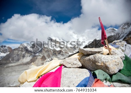Close up of buddhist prayer flags with snow covered mountain peaks and blue sky in the background in the Himalayas, Nepal during the summer months