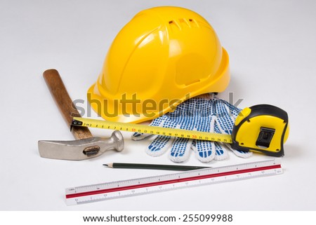 close up of builder's work tools and yellow helmet over white background - stock photo