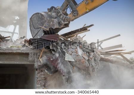 Close up of building demolition by excavator arm. Backhoe demolishing house. - stock photo