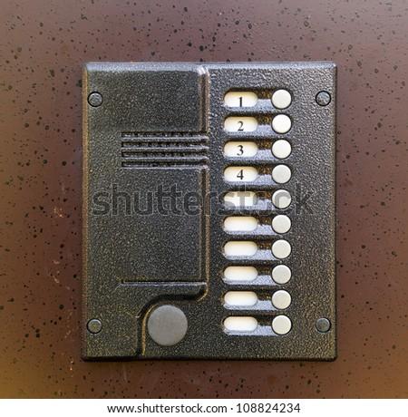 Close-up of building intercom in steel door - stock photo