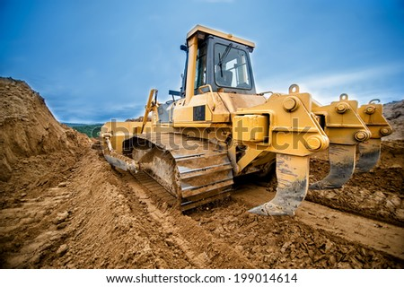 close-up of bulldozer or excavator working with soil on highway construction site  - stock photo