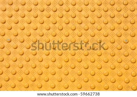 Close up of bumpy yellow patterned walkway. - stock photo
