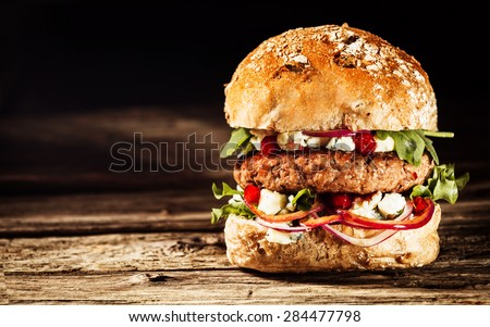 Close Up of Burger Piled High with Fresh Toppings on Whole Grain Artisan Bun, on Rustic Wooden Surface with Dark Background and Copy Space - stock photo