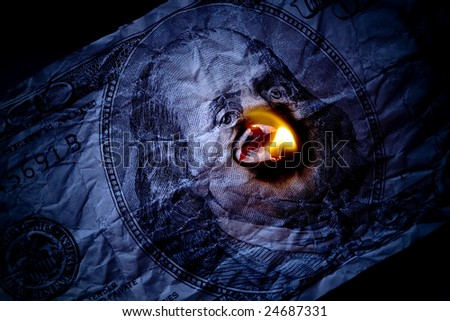Close up of burning one hundred dollars bank-note with portrait of Benjamin Franklin - stock photo