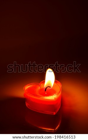 Close Up of burning red candle heart on dark background