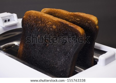 Close-up of burnt toasts in a toaster - stock photo