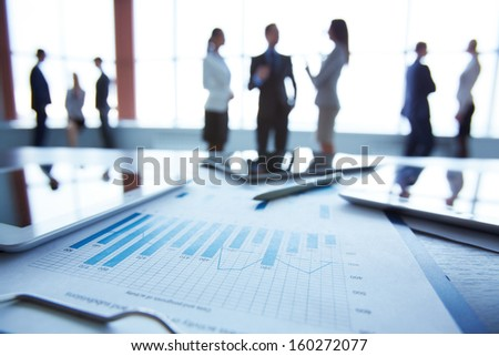 Close-up of business document in clipboard at workplace on background of office workers interacting