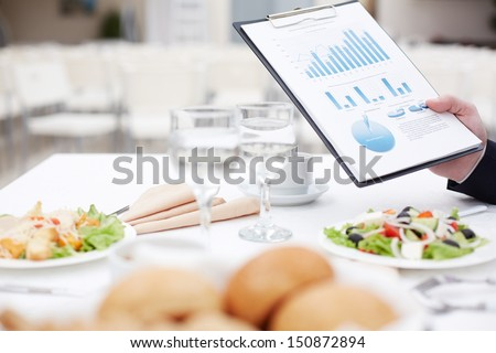 Close-up of business document in male hand during business lunch - stock photo