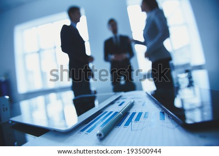 Close-up of business document, pen and touchpads at workplace on background of office workers interacting - stock photo