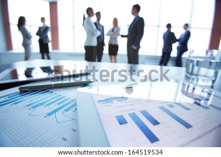 Close-up of business electronic and paper documents on the desk, office workers interacting in the background - stock photo