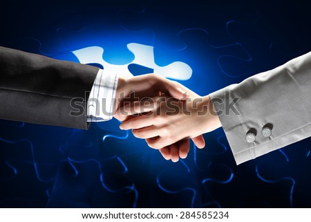 Close up of business handshake with puzzle elements at background