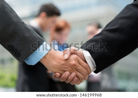 Close-up of business handshaking on the foreground - stock photo