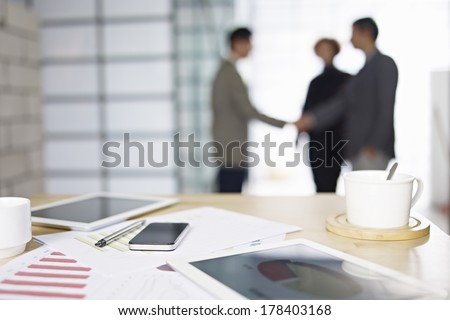 close-up of business items with people meeting in background. - stock photo