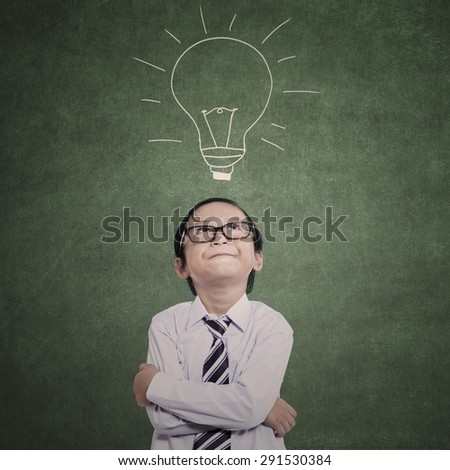 Close-up of business kid on lamp drawing in the class - stock photo