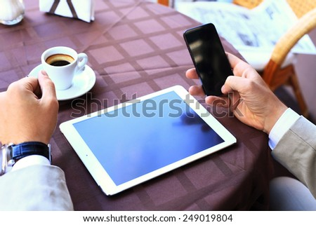 Close-up of business male hands touching digital tablet, formal businessman with cup of coffee on table - stock photo