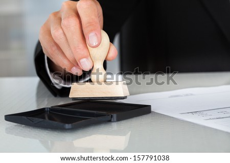 Close-up Of Business Man Hand Pressing Rubber Stamp On Document - stock photo