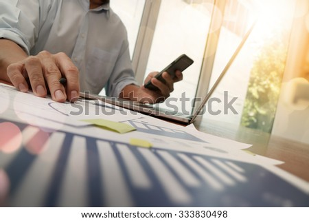 close up of business man hand working on laptop computer with digital layer business graph information diagram on wooden desk as concept - stock photo