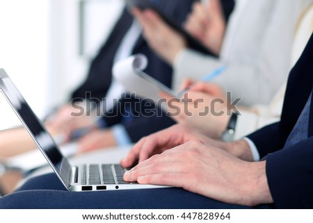 Close-up of business man hands typing on laptop computer at the conference - stock photo