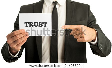 Close up of business man holding a white card saying Trust. Isolated on white background. - stock photo