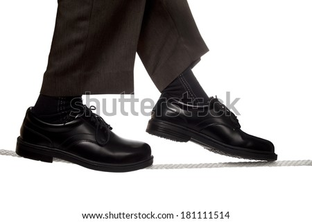 Close up of business man walking a tight rope - stock photo