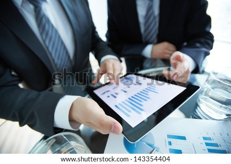 Close-up of business partners discussing document in touchpad - stock photo