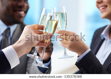 Close-up of business partners hands cheering up with flutes of golden champagne - stock photo