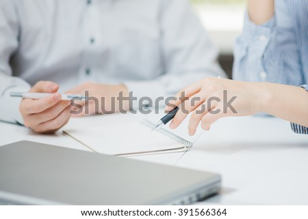 Close-up of business partners' hands over papers at a meeting