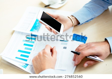 Close-up of business people analyzing financial data on documents and a smartphone - stock photo