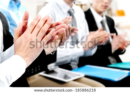 Close-up of business people clapping hands. - stock photo