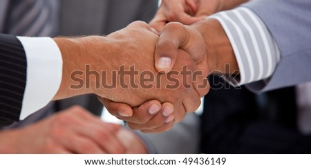 Close-up of business people closing a deal in a meeting