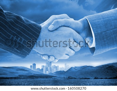 Close-up of business people handshaking on background of buildings and landscape - stock photo