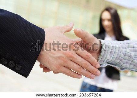 Close-up of business people handshaking on background of businesswoman and office building - stock photo