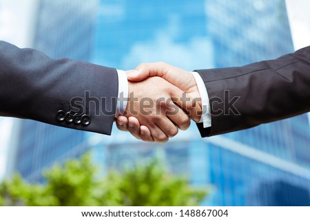 Close-up of business people handshaking on background of modern building - stock photo
