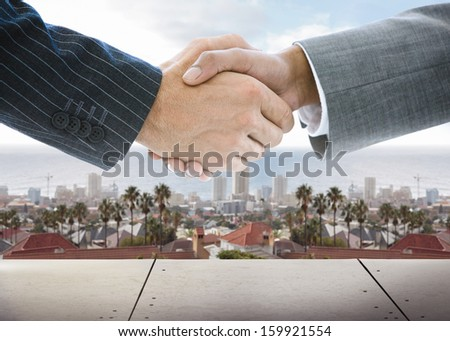 Close-up of business people handshaking on background of town scape - stock photo