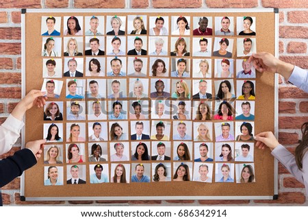 Close-up Of Business People Hiring The Candidates Attached On Corkboard For Job