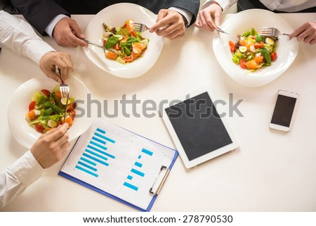 Close-up of business people in formalwear enjoying salads. Business lunch. - stock photo