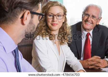 Close up of business people listening to colleague and smiling