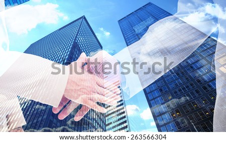Close up of business people shaking their hands against skyscraper