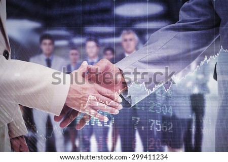 Close up of business people shaking their hands against stocks and shares - stock photo