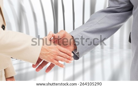 Close up of business people shaking their hands against white room with large window overlooking city - stock photo