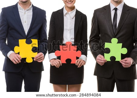 Close-up of business people wanting to put pieces of puzzle together.