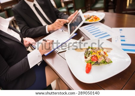 Close-up of business people working on marketing strategy during business lunch. - stock photo